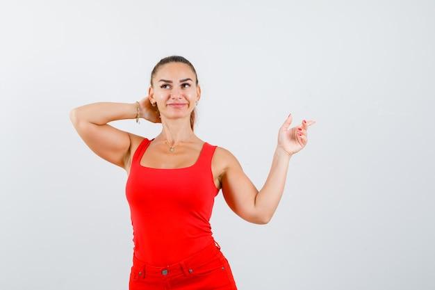 Piękna młoda kobieta, wskazując w prawym górnym rogu, trzymając rękę za głową w czerwonym podkoszulku, spodniach i marzycielski wygląd. przedni widok.