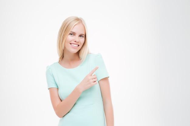 Piękna młoda kobieta wskazuje jej palec. uśmiechnij się i patrz na przód odizolowany na białej ścianie