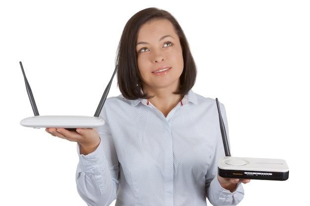 Piękna młoda kobieta wybierająca między dwoma bezprzewodowymi routerami z modemem sprzęt w jej rękach na białym tle