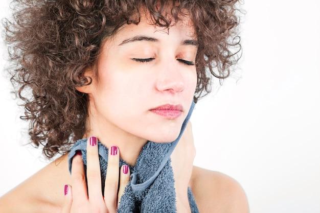 Piękna młoda kobieta wyciera jej twarz z pieluchą przeciw białemu tłu