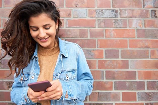 Piękna młoda kobieta wysyła wiadomość tekstową