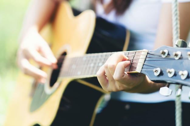 Piękna młoda kobieta z acustic gitarą przy naturą