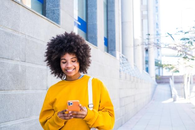 Piękna młoda kobieta z afryki lub ameryki spaceruje po ulicy miasta, patrząc na swój telefon, uśmiechając się i dobrze się bawiąc