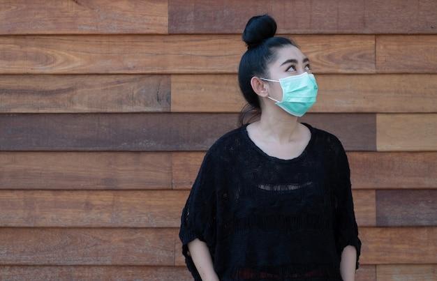 Piękna młoda kobieta z azji zakładająca maskę medyczną w celu ochrony przed chorobami układu oddechowego przenoszonymi przez powietrze, takimi jak grypa covid-19 pm2.5 pyłu i smogu na ścianie drewnianej ściany, koncepcja bezpieczeństwa kobiet dotycząca infekcji wirusowej