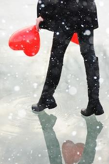 Piękna młoda kobieta z balonem w kształcie serca na zamarzniętej rzece