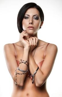 Piękna młoda kobieta z biżuterią na rękach na białym tle