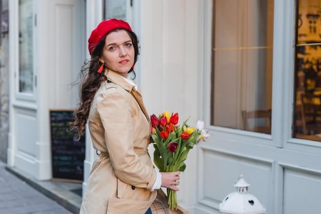 Piękna młoda kobieta z bukietem kwiatów tulipanów wiosna na ulicy miasta. szczęśliwa dziewczyna spaceru na świeżym powietrzu. wiosna portret ładnej kobiety na starym mieście