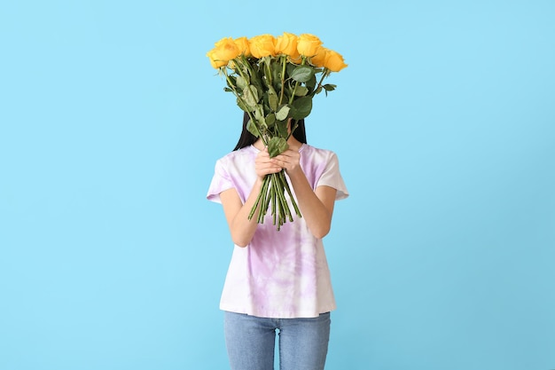 Piękna młoda kobieta z bukietem róż na powierzchni koloru