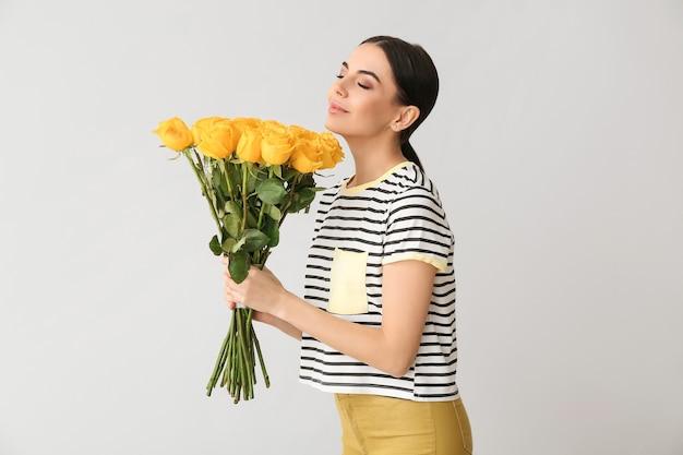 Piękna młoda kobieta z bukietem róż na szarej powierzchni