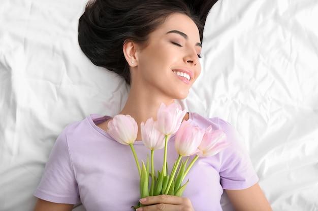 Piękna młoda kobieta z bukietem tulipanów, leżąc na łóżku