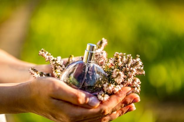 Piękna młoda kobieta z butelką kwiatowy perfum. zamyka up kobiet ręki pokazuje pachnidło.