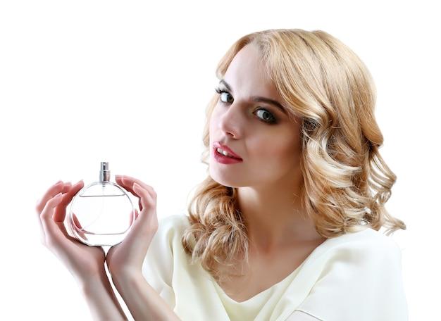Piękna młoda kobieta z butelką perfum izolować na białym