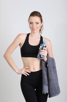 Piękna młoda kobieta z butelką wody i ręcznikiem