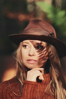 Piękna młoda kobieta z cieniem liści na twarzy