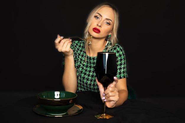Piękna młoda kobieta z czerwoną szminką na ustach trzyma kieliszek wina i złota rybka biżuteria. strzał studio.