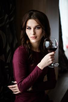 Piękna młoda kobieta z czerwonym winem. piękna dziewczyna z lampka
