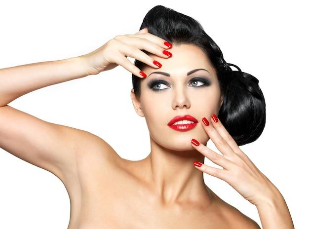 Piękna młoda kobieta z czerwonymi paznokciami i makijaż moda - na białym tle na białej ścianie