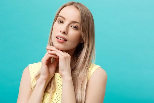 Piękna młoda kobieta z czystą idealną skórą. portret piękna modelka dotyka jej twarzy. spa, pielęgnacja skóry i wellness. zamknij się, niebieskie tło, lato.