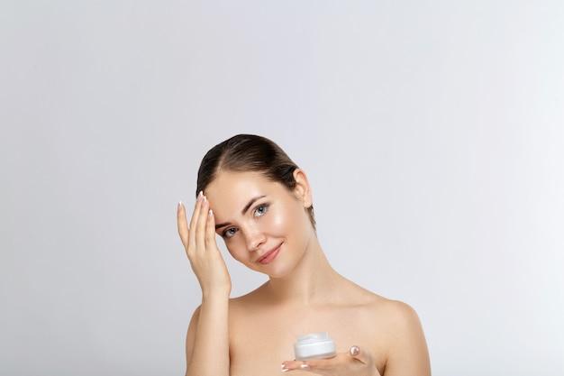 Piękna młoda kobieta z czystą, świeżą skórą dotyka własnej twarzy. zabieg na twarz. ochrona skóry. kosmetologia, uroda i spa.