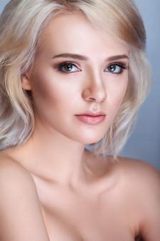 Piękna młoda kobieta z czystą, świeżą skórą dotyka własnej twarzy, zabiegu na twarz, kosmetologii, urody i spa,