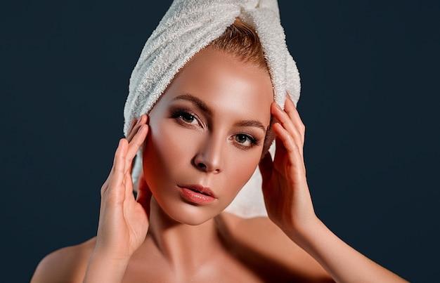 Piękna młoda kobieta z czystą, świeżą skórą dotyka własnej twarzy