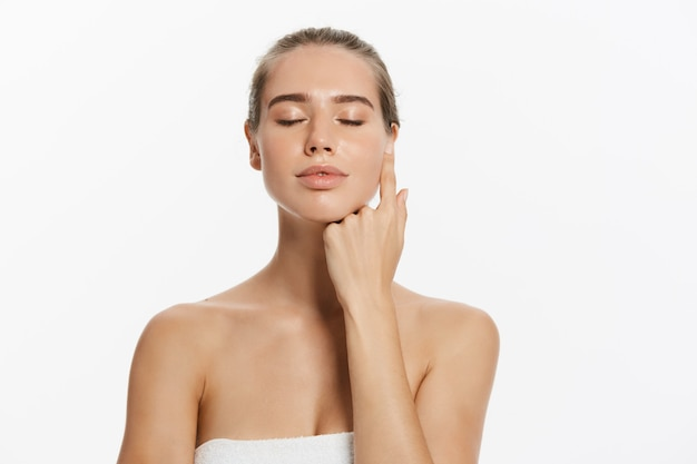 Piękna młoda kobieta z czystą świeżą skórą dotykać własnej twarzy. zabieg na twarz.