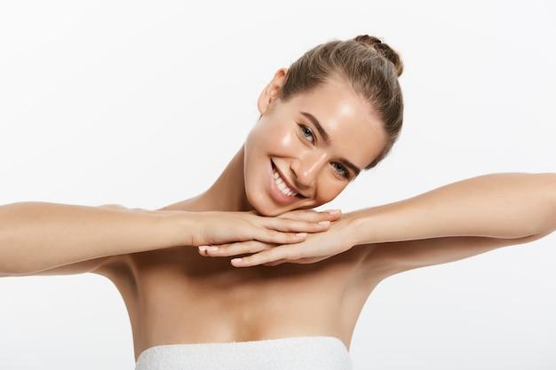 Piękna młoda kobieta z czystą świeżą skórą dotykać własnej twarzy.