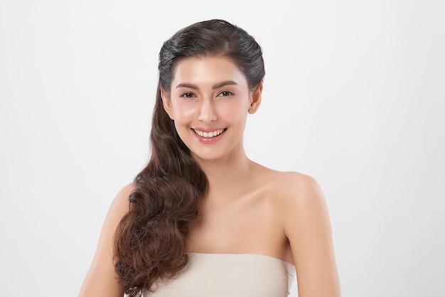 Piękna młoda kobieta z czystą, świeżą skórą na białej ścianie