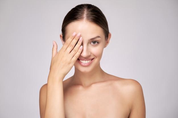 Piękna młoda kobieta z czystą, świeżą skórą stojącą na jasnoszarym tle