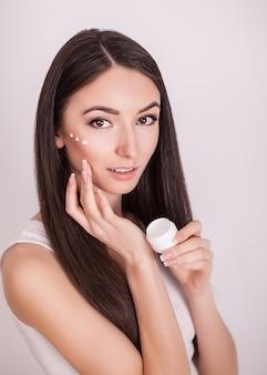 Piękna młoda kobieta z czystą, świeżą skórę dotyku twarzy