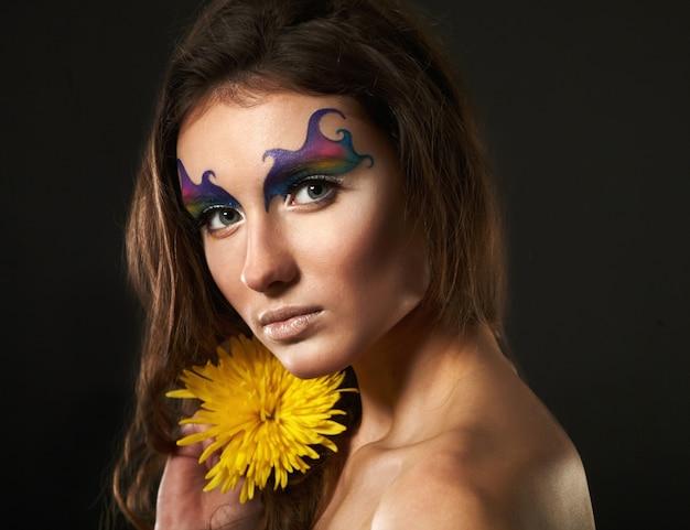 Piękna młoda kobieta z delikatnym kwiatem