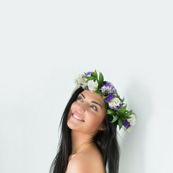 Piękna młoda kobieta z delikatnymi kwiatami we włosach