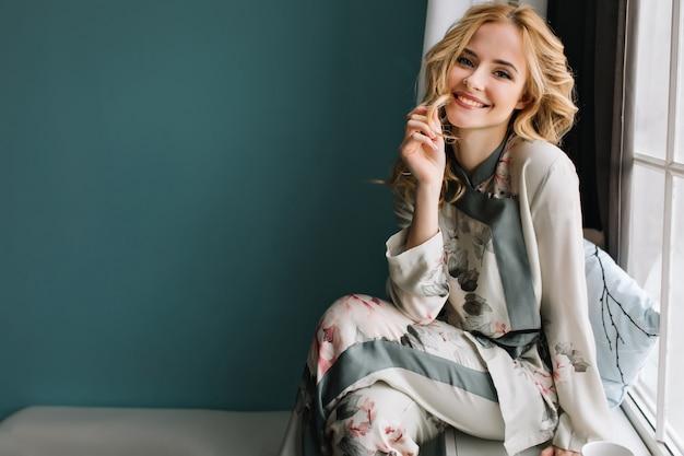 Piękna młoda kobieta z długimi blond falowanymi włosami siedzi na parapecie w pokoju z turkusową ścianą. uśmiecha się i cieszy poranek. ubrana w ładną piżamę.