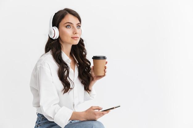 Piękna młoda kobieta z długimi kręconymi włosami brunetka na sobie białą koszulę siedzącą na białym tle nad białą ścianą, ciesząc się słuchaniem muzyki przez słuchawki podczas korzystania z telefonu komórkowego i picia takeaw