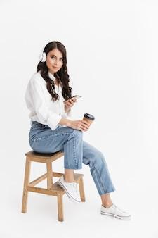 Piękna młoda kobieta z długimi kręconymi włosami brunetka na sobie białą koszulę siedzącą na białym tle nad białą ścianą, ciesząc się słuchaniem muzyki przez słuchawki podczas korzystania z telefonu komórkowego