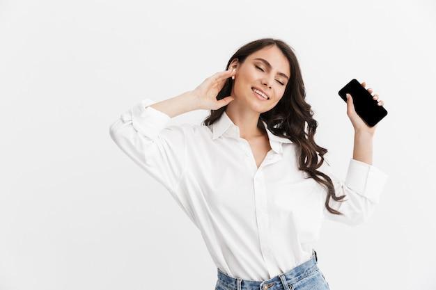 Piękna młoda kobieta z długimi kręconymi włosami brunetka na sobie białą koszulę stojącą na białym tle nad białą ścianą, ciesząc się słuchaniem muzyki przez słuchawki, trzymając pusty ekran telefonu komórkowego
