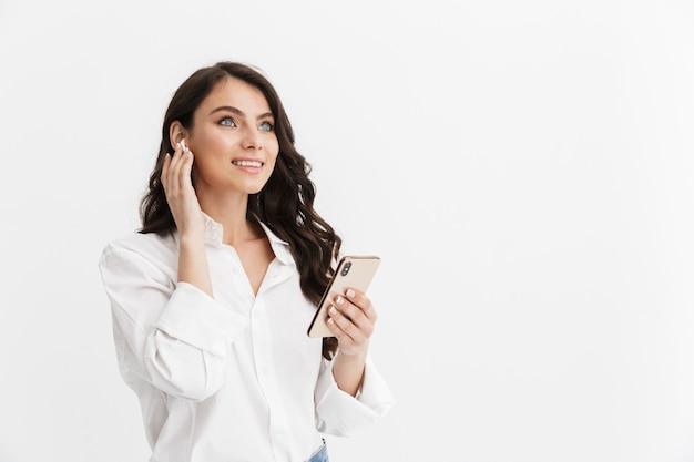 Piękna młoda kobieta z długimi kręconymi włosami brunetka na sobie białą koszulę stojącą na białym tle nad białą ścianą, ciesząc się słuchaniem muzyki przez słuchawki, trzymając telefon komórkowy