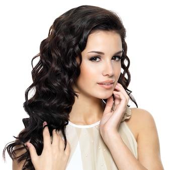 Piękna młoda kobieta z długimi kręconymi włosami piękna. portret modelka na białym tle
