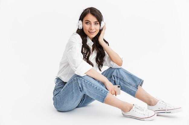 Piękna młoda kobieta z długimi kręconymi włosami, ubrana w białą koszulę, siedząca na białym tle nad białą ścianą, ciesząca się słuchaniem muzyki przez słuchawki