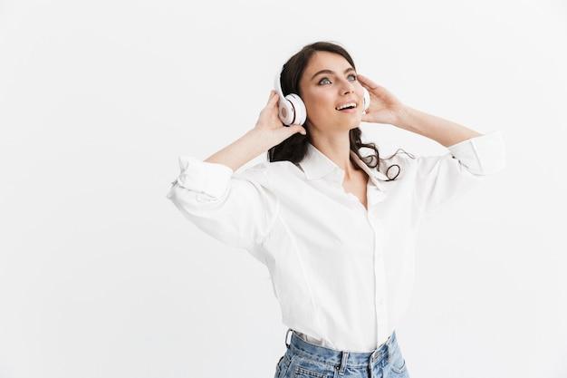 Piękna młoda kobieta z długimi kręconymi włosami, ubrana w białą koszulę, stojąca na białym tle nad białą ścianą, ciesząca się słuchaniem muzyki przez słuchawki