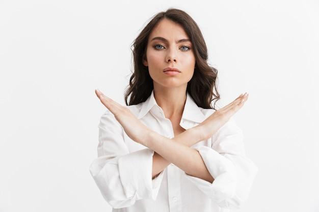 Piękna młoda kobieta z długimi kręconymi włosami, ubrana w białą koszulę, stojącą na białym tle nad białą ścianą, pokazując gest zatrzymania