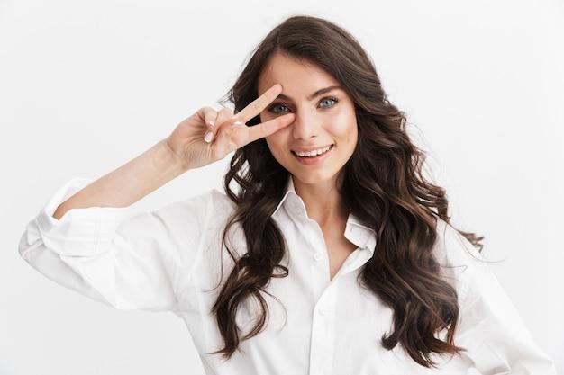 Piękna młoda kobieta z długimi kręconymi włosami, ubrana w białą koszulę, stojąca na białym tle nad białą ścianą, pokazująca gest pokoju