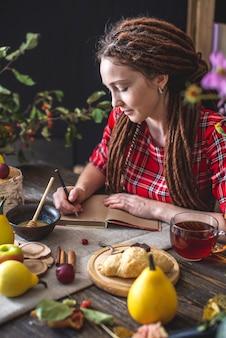 Piękna młoda kobieta z dredami pisze w zeszycie