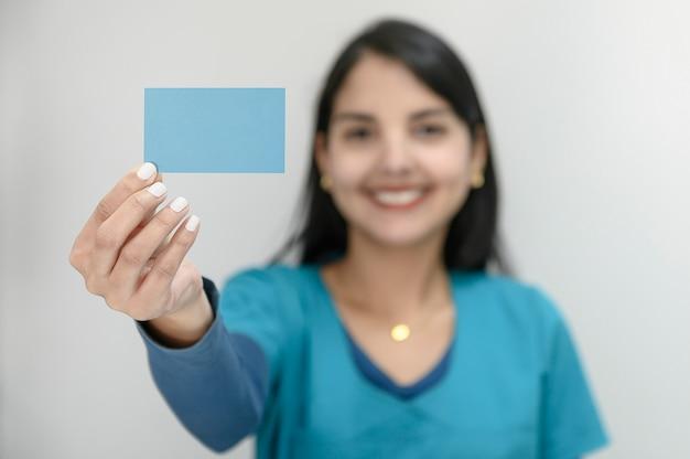 Piękna młoda kobieta z dużym uśmiechem wystawia pustą wizytówkę