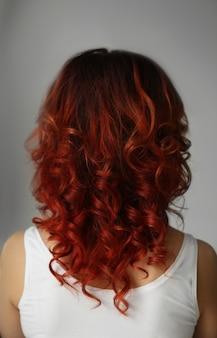 Piękna młoda kobieta z farbowanymi kręconymi włosami w pomieszczeniu