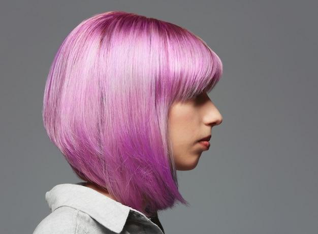 Piękna młoda kobieta z farbowanymi włosami na szarym tle