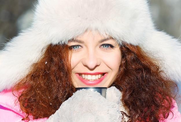 Piękna młoda kobieta z filiżanką gorącej herbaty na zewnątrz w zimowy dzień, zbliżenie