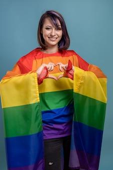 Piękna młoda kobieta z flagą lgbt. lesbijka z ufarbowanymi na fioletowo włosami i kolczykami, trzymająca flagę społeczności gejów i lesbijek