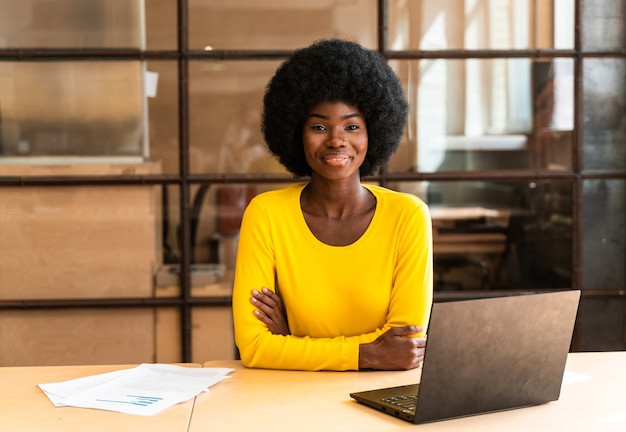 Piękna młoda kobieta z fryzurą afro pracująca w biurze