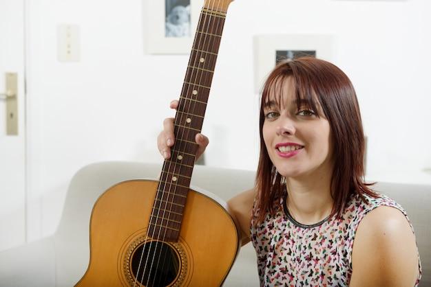 Piękna młoda kobieta z gitarą akustyczną